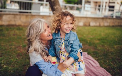 Loving grandmother and granddaughter playing and laughing together in garden